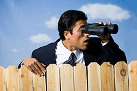 Businessman looking through binoculars over wooden fence
