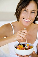 A woman in her 40s eating fruit in bed.