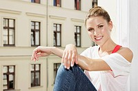 Germany, Berlin, Young woman sitting at open window, smiling, portrait