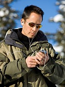 Man outdoors in winter with mp3 player smiling