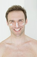Man with moisturizer on face, portrait, smiling