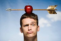 Man outdoors with arrow through red apple on head