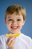 Closeup of boy eating orange wedge