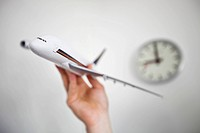 Close_up of hand holding model airplane