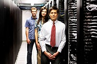 Portrait of three business people in a server room