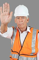 Portrait of confident male construction worker with stop gesture over gray background