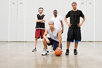 four men in athletic clothing on basketball court