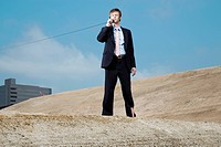 Businessman standing on construction site holding telephone receiver, low angle view