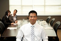 Portrait of businessman in boardroom, out of focus coworkers behind