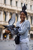 Woman in square with pigeon on head smiling