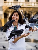 Woman with pigeons and eyes crossed with tongue out