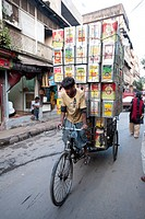 Cycle rickshaw carrying huge load of oil cans through market, Kolkata Calcutta, West Bengal, India, Asia