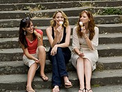 Three women sitting on steps outdoors eating ice cream cones smiling