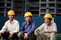 Three male construction workers with helmets outdoors smiling