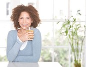 Woman smiling holding glass of fresh orange juice
