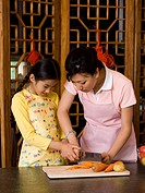 Woman and girl in aprons chopping vegetables