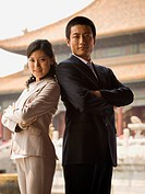 Businessman and woman standing with arms crossed and backs together with pagoda in background