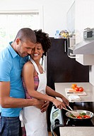 Man embracing woman cooking at stovetop