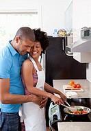 Man embracing woman cooking at stovetop