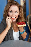 Young beautiful woman eating a strawberry tart.