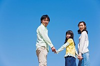 Portrait of family including young girl against clear blue sky