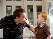 son feeding his father a piece of bread