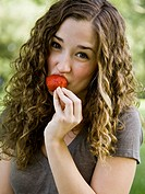 young woman eating a berry