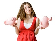 woman holding two halves of a broken piggy bank