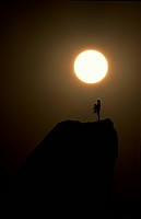 Silhouette of a couple standing on the mountain peak