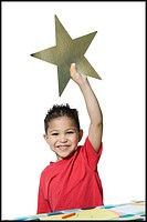 Portrait of a boy holding a star
