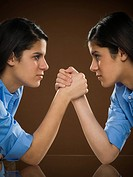 Profile of two teenage girls arm wrestling