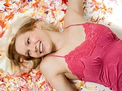 High angle view of a young woman lying on flower petals