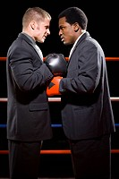 Profile of two businessmen staring at each other in a boxing ring
