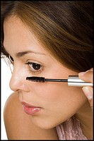 Close_up of a woman applying mascara on her eyelashes
