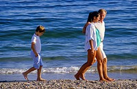 Moody boy walking behind couple with pregnant woman on seashore