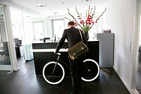 Businessman with his bike at the office reception