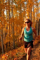 Woman running on trail thru aspens in fall