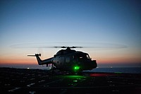 military helicopter landing at dusk