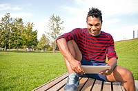 A young man using a tablet device outside.