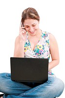 A pretty young woman sitting on floor with laptop and mobile pho
