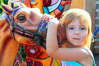 blond girl with fairground horse enjoy in park