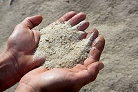 gravel sand in man hands in quarry background