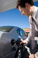 Businessman filling his car with gas