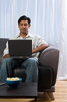 Man sitting on a sofa and using a laptop