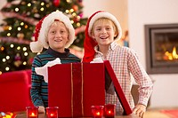 Two young boys opening a Christmas present on Christmas day