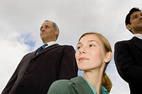 Low angle view of two businessmen and a businesswoman smiling