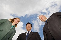 Low angle view of two businessmen and a businesswoman standing