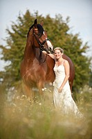 Woman wearing a wedding dress with a Hanoverian horse in a meadow
