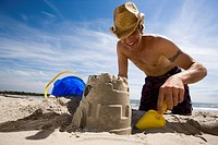 Low angle view of a young man digging sand on the beach