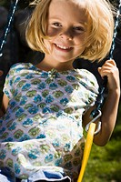 Portrait of a girl sitting on a swing
